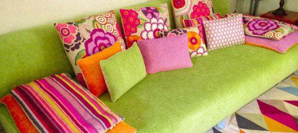 canapé multicolore avec coussins roses et verts